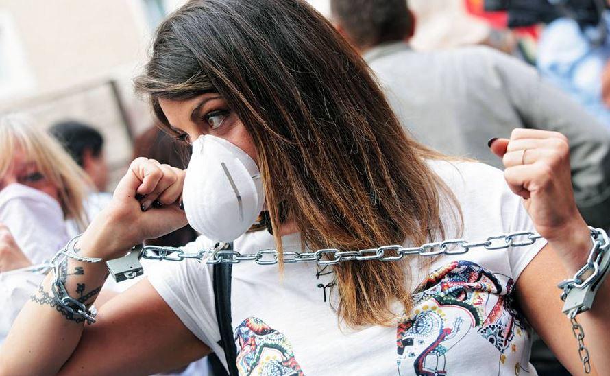 Una manifestante incatenata in dissenso per la riforma della Scuola