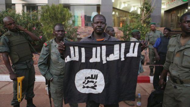 Maliani mostrano la bandiera portata dai terroristi durante il massacro in Mali