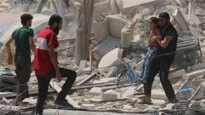 Un bambino viene portato via da un edificio crollato ad Aleppo