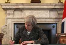Theresa May mentre firma la notifica su Brexit