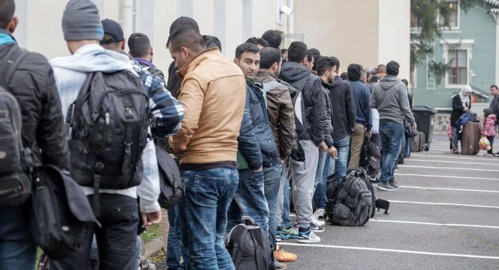 immigrati in fila