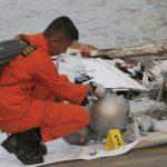 Un soccorritore davanti ai resti dell'aereo in Indonesia